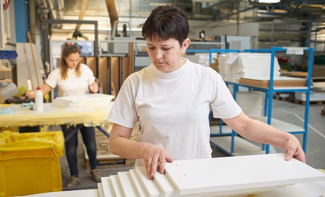 Dřevojas, paní skládá dřevěné desky